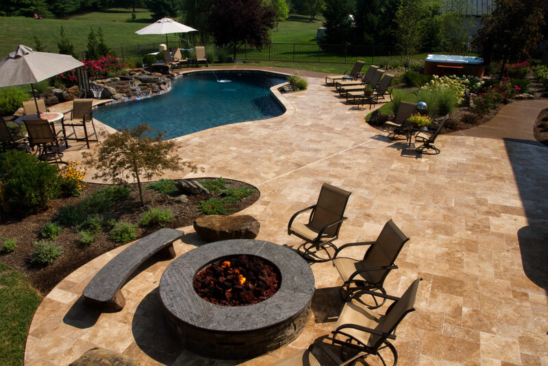 fire pit, patio, pool, and waterfall